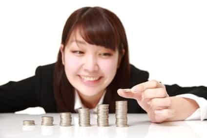 お金を積み上げてる女性画像